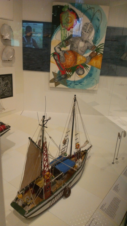 A model pearling lugger in the foreground with a Marie Jose oil painting behind in the transition between stories on the marine harvesting industries and Torres Strait in World War Two
